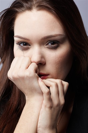 portrait of beautiful crying girl with smeared mascara hiding her face in hands Stock Photo - 7419229