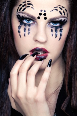 close up portrait of girl with spider bodyart of face zone and black finger-nails photo