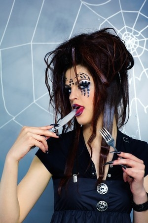 portrait of girl with spider bodyart of face zone with knife and fork photo