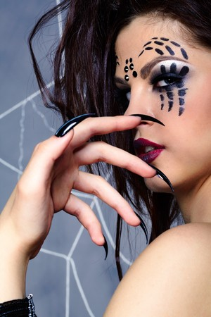 portrait of girl with spider bodyart of face zone looking over her shoulder photo