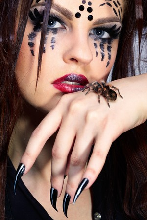portrait of girl with spider Brachypelma smithi bodyart of face zone photo