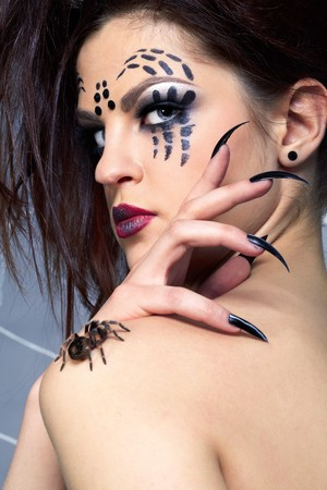 portrait of girl with spider bodyart of face zone posing with real spider Brachypelma smithi on her shoulder photo