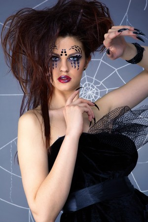portrait of girl with spider bodyart of face zone posing around the web photo