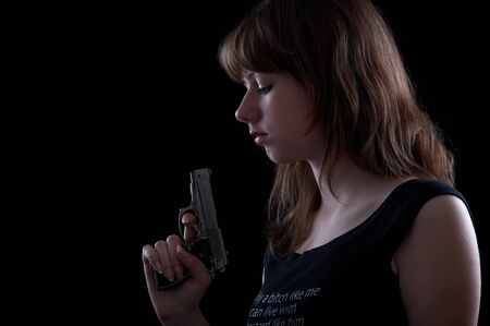 lonliness: Girl with gun isolated at the black background