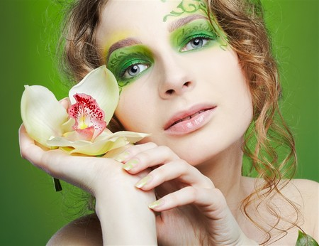 portrait of beautiful girl with fairy theme bodyart posing with lily flower Stock Photo - 7468654