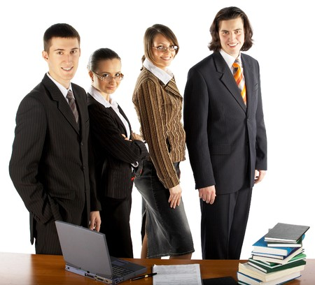 business team with laptop and books near the table photo