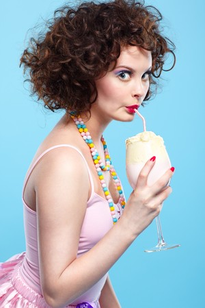 portrait of beautiful curly brunette girl with the glass of milk shake photo