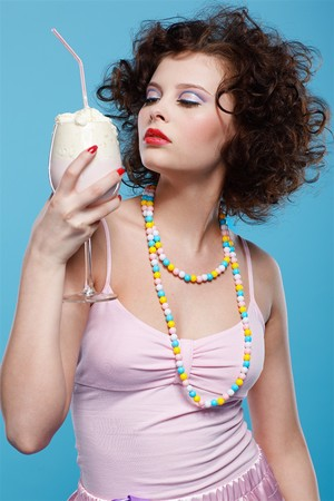 milk shake: portrait of beautiful curly brunette girl with the glass of milk shake
