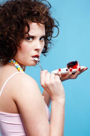 portrait of beautiful curly brunette girl tasting cake Stock Photo - 7486476