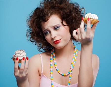 portrait of beautiful curly brunette girl choosing one of two tarts photo