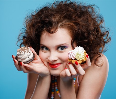 portrait of beautiful curly brunette girl with two tarts photo