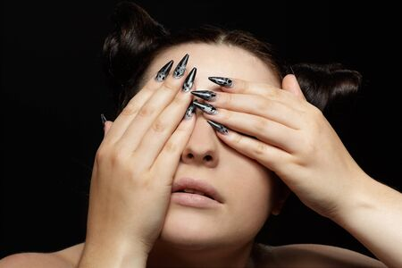 portrait of girl closing her eyes with manicured fingers photo