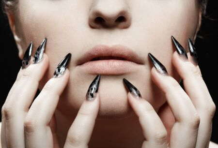 close-up portrait of girls lower part of face and manicured fingers photo