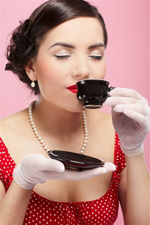 pin-up style portrait of beautiful brunette girl with tea cup photo