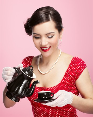 pin-up style portrait of beautiful brunette girl with teapot and cup photo