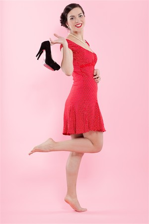 court shoes: pin-up style portrait of beautiful brunette girl standing a-tiptoe with court shoes in her hands Stock Photo