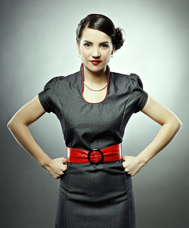 black belt: pin-up style portrait of beautiful brunette girl posing on gray