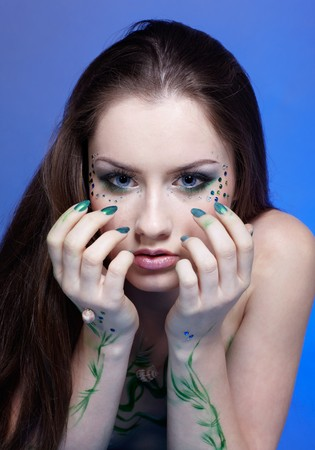 portrait of beautiful girl with mermaid bodyart on blue photo