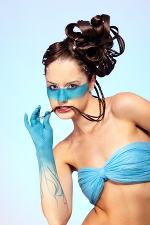 portrait of beautiful girl with blue stripe facial bodyart and fantasy hair-do with several thin braids photo