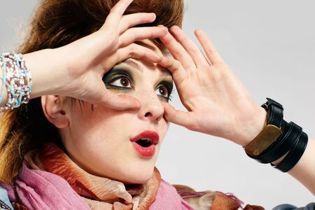portrait of glam punk redhead girl looking through her hands like binocular photo