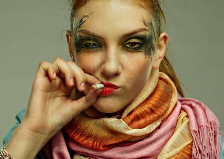 portrait of glam punk redhead girl smoking cigarette photo