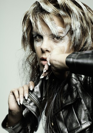 portrait of beautiful dark blonde girl with paint-like bodyart posing in leather jacket  photo
