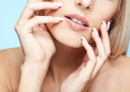 close-up portrait of beautiful girls lower part of face and manicured fingers photo