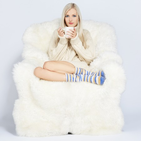 portrait of beautiful blonde sitting with cup on big white furry arm-chair photo