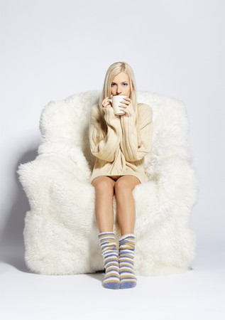 portrait of beautiful blonde sitting with cup on big white furry arm-chair Stock Photo - 7767917