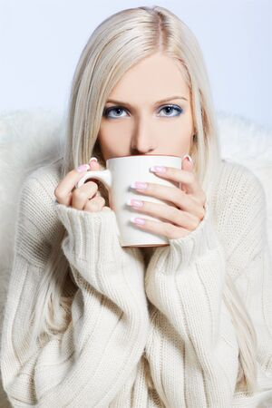 portrait of beautiful blonde with cup of hot drink photo