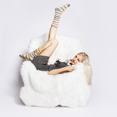 portrait of beautiful blonde sitting on big white furry arm-chair and putting on long striped socks Stock Photo - 7767882