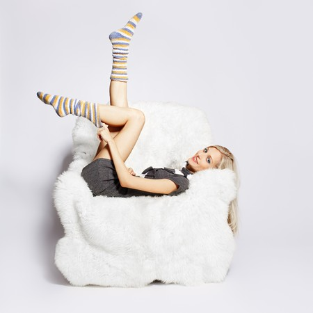 portrait of beautiful blonde sitting on big white furry arm-chair and putting on long striped socks Stock Photo