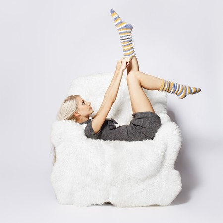 portrait of beautiful blonde sitting on big white furry arm-chair and putting on long striped socks Stock Photo - 7767890