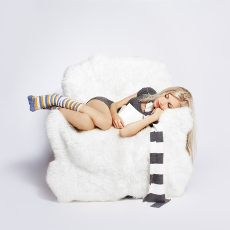 portrait of beautiful blonde sleeping with book in big white furry arm-chair photo