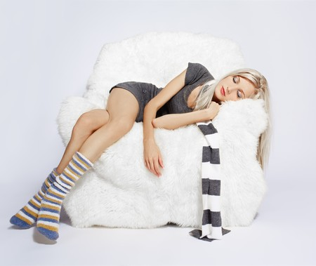 portrait of beautiful blonde sleeping on big white furry arm-chair photo