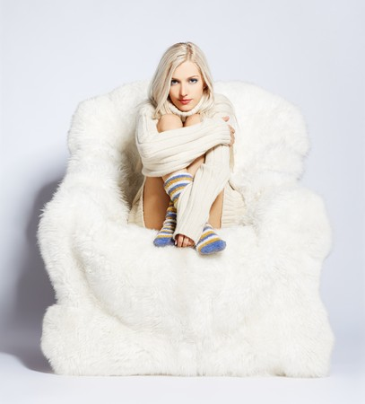 portrait of beautiful blonde sitting on big white furry arm-chair Stock Photo - 7767893