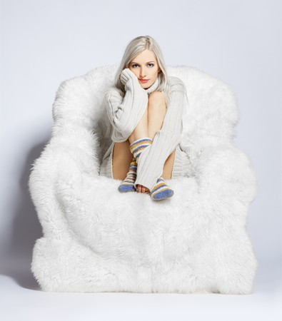 portrait of beautiful blonde sitting on big white furry arm-chair photo