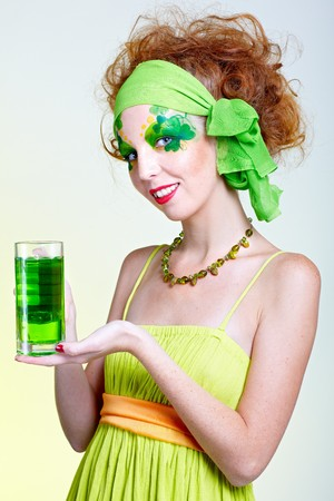 portrait of beautiful red-haired model with shamrock body art with the glass of green beer photo