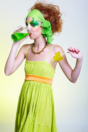 portrait of beautiful red-haired model with shamrock body art drinking green beer photo