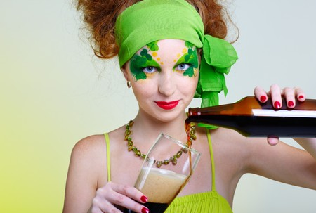 portrait of beautiful red-haired model with shamrock body art pouring glass with stout photo