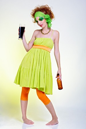 portrait of beautiful red-haired model with shamrock body art holding the glass of beer photo