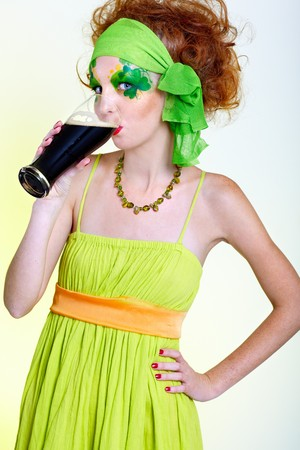 portrait of beautiful red-haired model with shamrock body art drinking stout photo