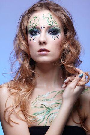 portrait of beautiful girl with bodyart of algae posing on blue photo