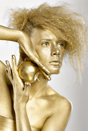 body paint: Chica dorada con manzana dorada en manos  Foto de archivo