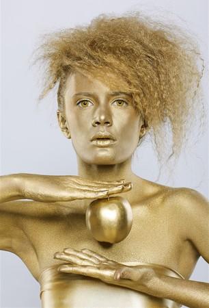 portrait of girl with golden bodyart posing with golden apple in her hands on gray photo