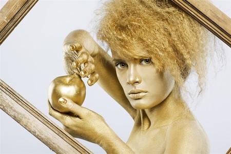 body paint: Retrato de una chica con oro bodyart posando con manzana dorada en su manos en marco de imagen en gris  Foto de archivo