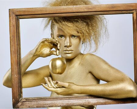 portrait of girl with golden bodyart posing with golden apple in her hands in picture frame on gray photo