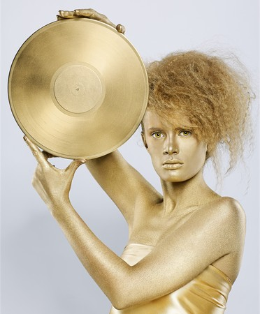portrait of girl with golden bodyart holding golden vinyl disc in hands on gray photo
