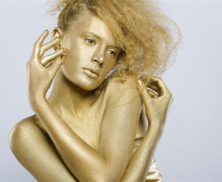 expresion corporal: Retrato de una chica con bodyart oro en gris  Foto de archivo