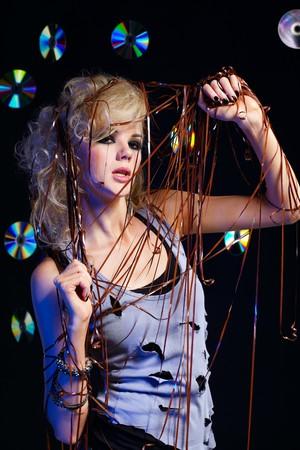 enmesh: potrait of beautiful blonde girl glam rocker gets entangled in audio tape. multiple shiny cds on dark background.